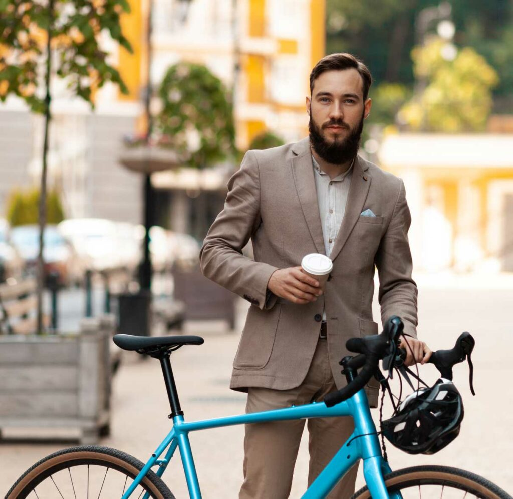 A business man having a coffee and holding a blue bike