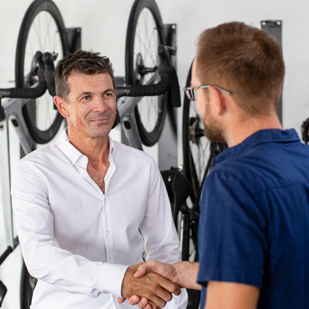 Two men shaking hands in a bike store