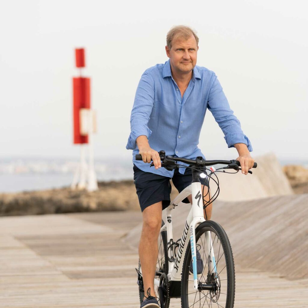Founder Till Kraemer riding a white bike